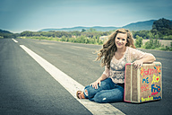 Young woman hitchhiking at empty street - ABAF001339