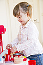 Little girl playing with children's kitchen - LVF001177