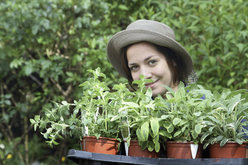 Portrait of young woman with seeldings for vegetable garden - SGF000621