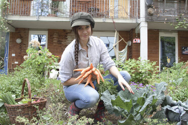 Young woman with carrots in vegetable garden - SGF000633