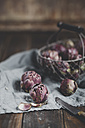 Wire basket of baby artichokes and knife on cloth and wooden table - SBDF000804