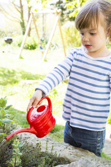 Little girl watering herbs in the garden - LVF001188