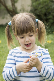 Portrait of little girl holding daisies in her hands - LVF001190