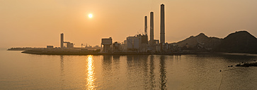 China, Hong Kong, Lamma Island, sunset over a coal-fired power plant in Yung Shue Wan bay - SHF001244