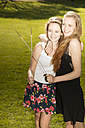 Two young female friends with sparklers in park - FCF000169