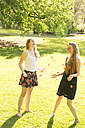 Two young female friends throwing petals in the air - FCF000170