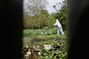 Look through wooden bars to woman wearing white protective overall mowing lawn - NDF000443