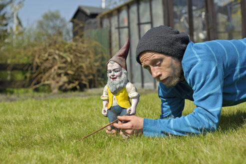 Portrait of man beside garden gnome - HACF000109
