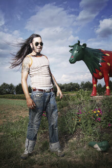 Portrait of a cool guy in front of a painted strawberry cow - IP000115