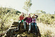 Three girls siting on rock in nature - HHF004808