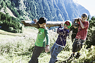 Three boys carrying log in the nature - HHF004820