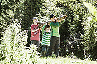 Three boys carrying log in the nature - HHF004822