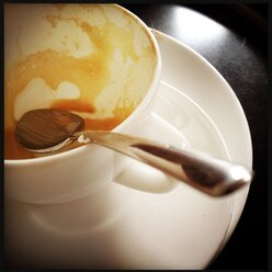 Coffee spoon in empty coffee cup with cappuccino residues - SRSF000470