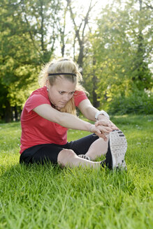 Young woman doing stretching exercise while sitting on meadow - BFRF000410