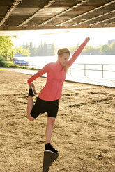 Young woman doing stretching exercise on one leg - BFRF000415