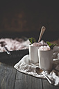 Two cups of pink lemonade granita with mint leaves on cloth and wooden table - SBDF000877