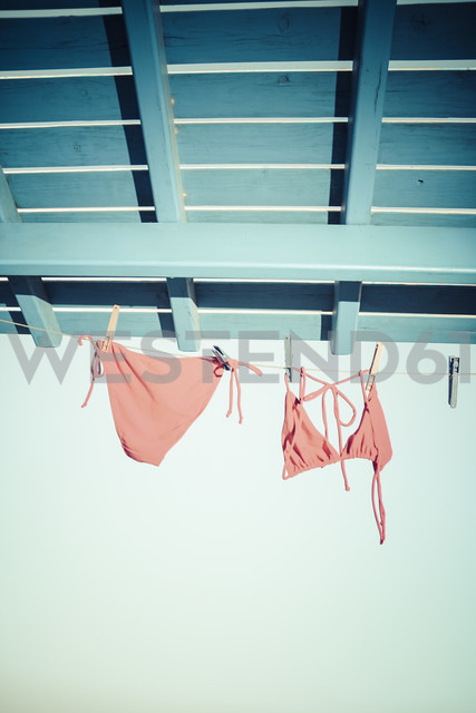 Bikini hanging on clothes line under the roof - KRPF000458