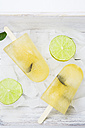 Two caipirinha ice lollies, ice cubes and slices of lime on white wood - LVF001221