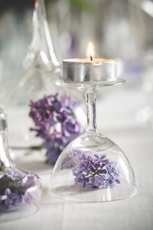 Table decoration with tea candles, glasses and lilac, Syringa, close-up - SBDF000894