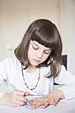 Portrait of little girl painting with wax crayon - LVF001225