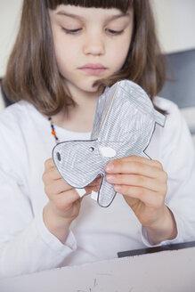 Portrait of little girl tinkering paper hippo - LVF001217