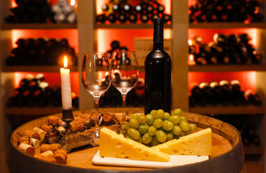 Private wine cellar with bottle of red wine, two wine glasses, grapes, cheese and lighted candle in foreground - JTF000547