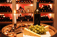 Private wine cellar with bottle of red wine, two wine glasses, grapes, cheese and lighted candle in foreground - JTF000548