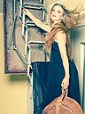 Portrait of young woman with old hatbox standing on attic ladder - FCF000197