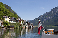 Austria, Upper Austria, Salzkammergut, Hallstatt, Lake Hallstaetter See and flag on boat - WWF003262