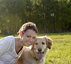 Portrait of young woman with Golden Retriever on meadow - BFRF000426