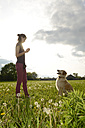 Portrait of young woman playing with Golden Retriever on meadow - BFRF000434