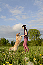 Young woman playing with Golden Retriever on meadow - BFRF000439