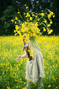 Little girl wearing country style dress throwing buttercups, Ranunculus, in the air - SARF000595