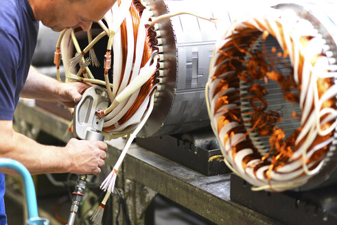 Electric motor production in a factory, worker installing copper wires - SCH000211