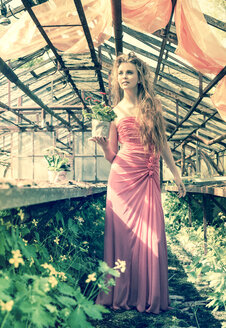Young woman wearing evening dress standing in old greenhouse - FCF000202