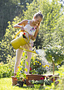Laughing teenage girl watering potted plants in the garden - WWF003295