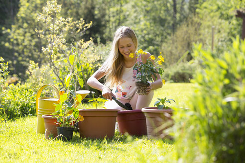 Smiling teenage girl repotting plants in the garden - WWF003297