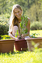 Portrait of smiling teenage girl repotting plant in the garden - WWF003299