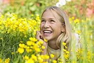 Portrait of happy teenage girl lying on a flower meadow - WWF003309