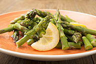 Green asparagus with slice of lemon on plate - CSTF000336