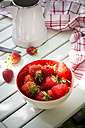 Bowl of strawberries, kitchen towel and jar on white wood - LVF001246