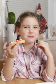 Portrait of little girl eating Christmas cookie - ECF000629
