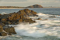 Australia, New South Wales, Tweed Shire, splashing breakwater at the rocky shore of Hastings Point in the first morning light - SHF001321