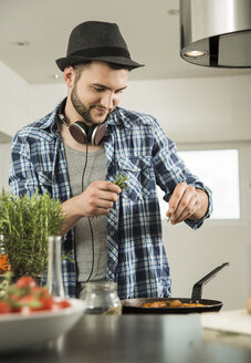 Young man cooking in kitchen at home - UUF000485