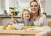 Portrait of mother and daughter baking in kitchen at home - UUF000537