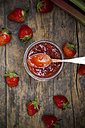 Glass of strawberry rhubarb jam, strawberries and rhubarb on dark wood, view from above - LVF001257