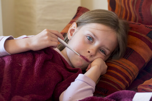 Little girl lying on couch with digital thermometer - SARF000627