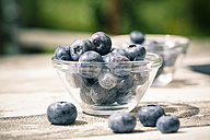 Glass bowls of blueberries on wooden table - SARF000611