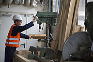 Young worker at carpentry of pallet production - SGF000695