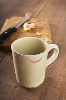 Empty cup of coffee with red lipstick track in front of knife and leftovers of Danish pastry on wooden board - CSTF000360